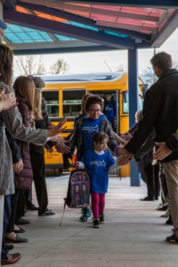 Positive Tomorrows students high-five friends on way into school