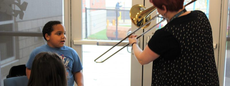 Mrs. Sarah plays the trombone for Positive Tomorrows student
