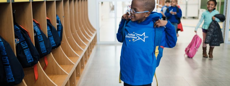 Positive Tomorrows student tries on backpack in hallway